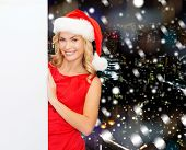 winter holidays, christmas, advertising and people concept - smiling young woman in santa helper hat with white blank billboard over snowy night city background