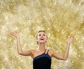 people, happiness, holidays and glamour concept - smiling woman raising hands and looking up over yellow lights background