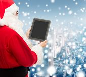 christmas, advertisement, technology, and people concept - man in costume of santa claus with tablet pc computer over snowy city background