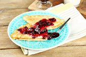 Delicious pancakes with berry jam on plate on wooden background