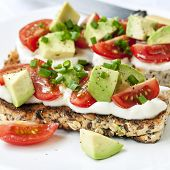 Sourdough toast with avocado, cherry tomatoes, cream cheese and chives.