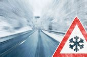 picture of slippery-roads  - Mountain road with snowfall and traffic sign - JPG