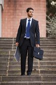 Businessman carrying his skateboard