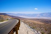 foto of bend over  - Winding asphalt road bends around a corner in the mountains over Death Valley National Park - JPG