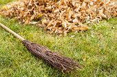 Fall clearing in garden - besom and a pile of leaves