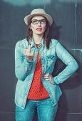Young Beautiful Girl In Red Jersey And Hat Showing Middle Finger