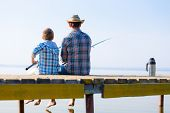 boy and his father fishing together from a pier