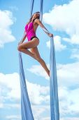 Young brunette woman gymnast on blue sky background.