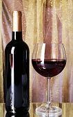 Red wine glass and bottle of wine on bright background