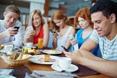 Friends sitting at caf�?�?�?�© absorbed in their phones