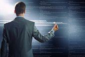 Rear view of businessman touching digital screen