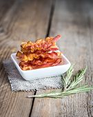 image of bacon strips  - Fried Bacon Strips With Fresh Rosemary On The Wooden Table - JPG