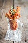foto of bacon strips  - Fried Bacon Strips With Fresh Rosemary On The Wooden Table - JPG