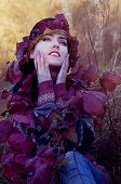 stock photo of pixie  - beautiful brunette in autumn red leaves looking like pixie - JPG
