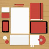 Empty red stationary set on wooden background (business cards, letterhead, envelope, notepad, phone, tablet, badge, cd, flash drive)