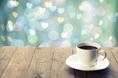 Cup of hot drink on bright background