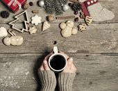 Christmas decorations, home made ginger bread and woman's hand on mulled wine on rustic wooden background