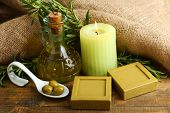 Bars of natural soap with rosemary and olive oil, candle and olives on wooden background