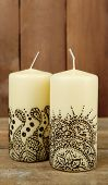 Beautiful candles with mehendi on wooden table