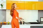 Happy young woman cooking in the kitchen at home. Healthy eating. Home interior. Furniture.