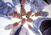 business, people and teamwork concept - smiling group of businesspeople standing in circle and showing thumbs up gesture