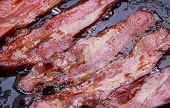 stock photo of bacon strips  - Bacon strips or rashers being cooked in frying pan - JPG