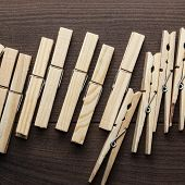 stock photo of pegging  - wooden clothes pegs on the brown table - JPG