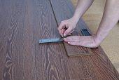 image of laminate  - Worker produces markup laminate flooring oak color chocolate - JPG