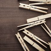 image of pegging  - wooden clothes pegs on the brown table - JPG
