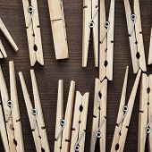 picture of pegging  - wooden clothes pegs on the brown table - JPG