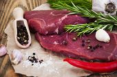 picture of beef shank  - Fresh beef steak with aromatic spices on a wooden background - JPG