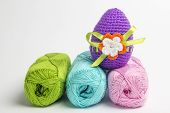 foto of boll  - Easter egg made of multicolored crochet yarn on a white background with bolls skeins and crochet hooks - JPG