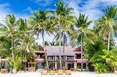 stock photo of boracay  - Luxury tropical villa near the sea with beautiful colourful decor surrounding palm trees and lounges in front of it on famous exotic white sandy beach on Boracay island station 1 Philippines - JPG