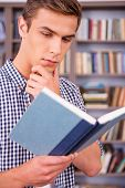 pic of concentration man  - Concentrated young man reading book and holding hand on chin while standing in library - JPG