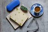 picture of bookworm  - Old book glasses a branch of pine needles cup of coffee and an envelope on the table - JPG