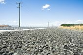 picture of south-pole  - Country road selective focus straight ahead through rural South Island New Zealand lined with power poles and lines on one side - JPG