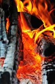 stock photo of ashes  - Bright flame of fire in dark with ashes - JPG