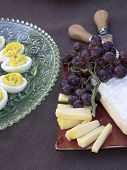 stock photo of brie cheese  - Deviled eggs, brie and gouda cheese with grapes served as horderves before dinner in decorative plates