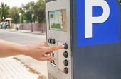 stock photo of meter  - Adult male hand push the buttons on parking meter - JPG