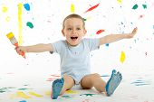 picture of floor covering  - Adorable 3 year old boy child creatively stains on the wall floor with colourful paint - JPG