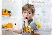 image of refrigerator  - Little cute boy looking at camera and eating banana near open fridge - JPG
