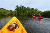 stock photo of kayak  - Family with kids paddling on colorful kayaks at mangroves during summer vacation - JPG