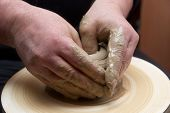 picture of molding clay  - Female hands forming clay pot on the pottery wheel