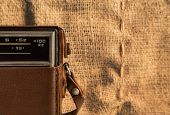 stock photo of transistor  - Part of an old transistor radio in a leather case on a background of a burlap - JPG