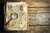 stock photo of hieroglyph  - Grunge papers with hieroglyphics with magnifier on wooden background - JPG