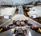image of slippery-roads  - Biker rides a motorcycle on a slippery road through a mountain pass in Norway - JPG