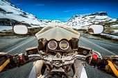 foto of slippery-roads  - Biker rides a motorcycle on a slippery road through a mountain pass in Norway - JPG