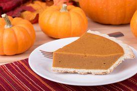 foto of pumpkin pie  - Slice of pumpkin pie with pumpkins in background - JPG