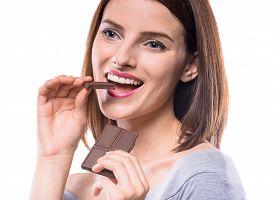 image of flirty  - Flirty beautiful woman eating bar of chocolate and looking away - JPG