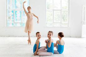 stock photo of ballerina  - Three little ballerinas with personal ballet teacher in dance studio - JPG